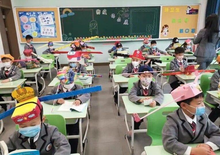 Ritorno a scuola: in Cina i bambini si costruiscono cappelli anti-contagio