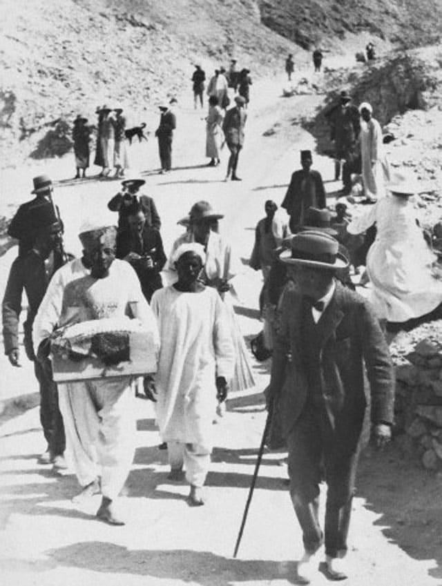 L'archeologo Howard Carter controlla i portatotio egiziani che trasportano al museo una preziosa statuetta della regina appena ritrovata nella tomba del faraone.